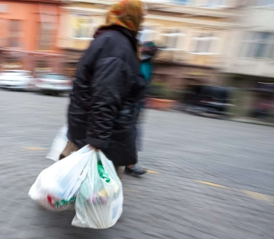 An old woman wearing a winter coat carries plastic bags down the street