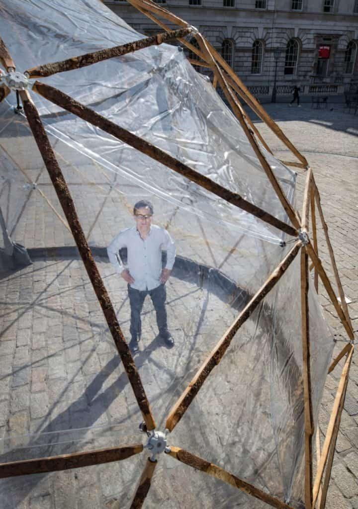 Michael PInsky posing inside Pollution Pods by Michael Pinsky