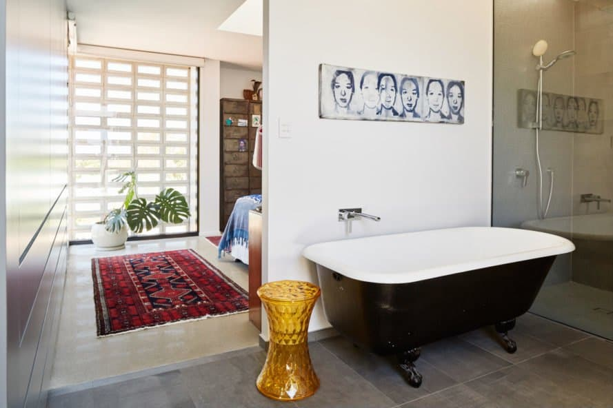 Bathroom with tub and gold vase