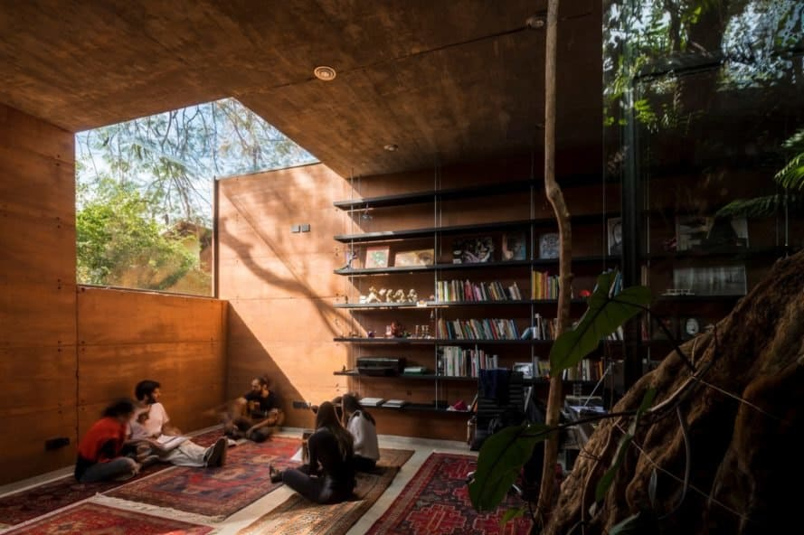 interior shot of rammed earth building with a book shelf and large window
