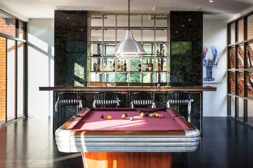 Pool table in front of a large home bar